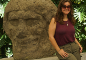 Image of a White woman wearing a tank top and sunglasses next to a stone statue of a head.